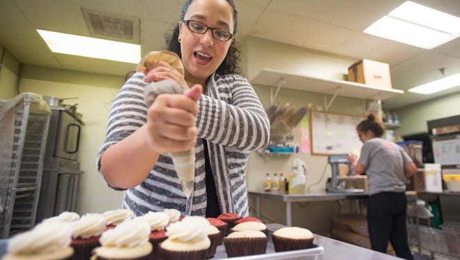 Promise Montoya applies frosting at Butter Cream Cupcakery on S. College Avenue on Monday, April 23, 2018. Montoya said she sometimes dreams of new flavor combinations for shops line of specialty cupcakes.