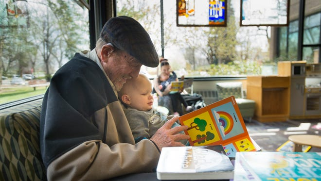 Bill Towle reads a book with his grandson, Russell, 2, at Old Town Library on Thursday, April 26, 2018. The Poudre River Public Library District is working on a master plan for future services and facilities.