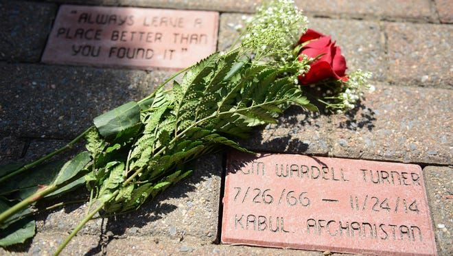 Roses lay on the newly installed bricks that have been placed in the James M. Bennett Memorial Garden in memory of SGM. Wardell Turner, a James M. Bennett High graduate, that was killed in Afghanistan in 2014 while serving his country in the Army on Thursday, May 3, 2018.