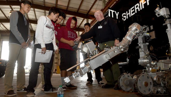 Mike Harris, of the Ventura County Sheriff's Office, teaches Santa Paula High School student Angel Donaire how to control an explosive ordnance robot during the Maritime Advanced Systems & Technology Open House and Technology Expo on Wednesday.