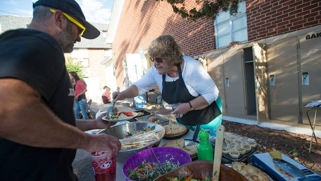 Elaine Branjord with the Fort Collins Democratic Socialists of America chapter serves food in front of a set of lockers at the Fort Collins Mennonite Fellowship on Friday, June 1, 2018. The group threw a party to celebrate after raising money to provide lockers for homeless people.