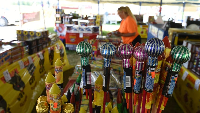 Big Eagle Discount Fireworks employee Christie Chamberlin stocks bottle rockets at the company's tent just outside the Mountain Home city limits on Tuesday. Rockets are one of the leading causes of fireworks injuries.