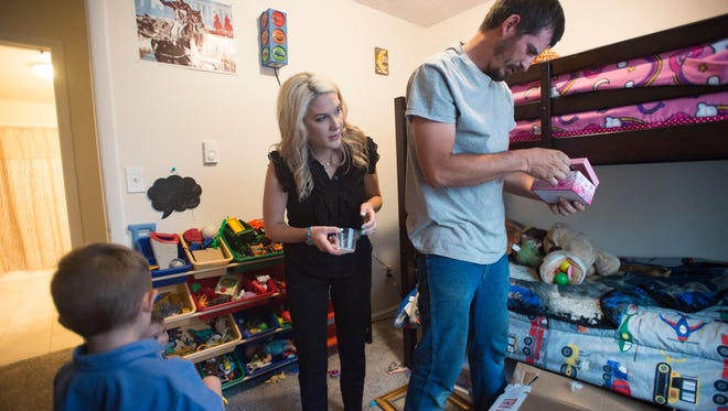 Cody and Sierra Briggs unpack picture frames and keepsakes at their new home in Wellington on Thursday, July 5, 2018. The Briggs family searched for a home in their budget for a few years before re-locating to Wellington from Fort Collins.