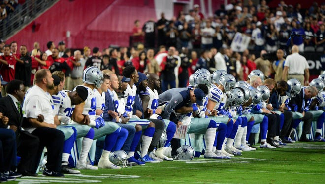 Members of the Cowboys take a knee before the national anthem before a game against the Cardinals on Sept. 24, 2017, at University of Phoenix Stadium.