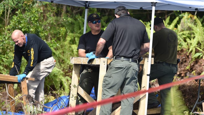 St. Lucie County sheriff's officials continue to sift through a wooded area on the south side off Kitterman Road on Thursday, July 12, 2018, while excavating what is believed to be human remains.