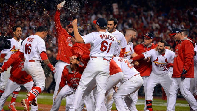 Cardinals second baseman Kolten Wong (16) is mobbed by teammates at home plate after hitting the walk-off solo home run against the San Francisco Giants during the 9th inning in NLCS Game 2.