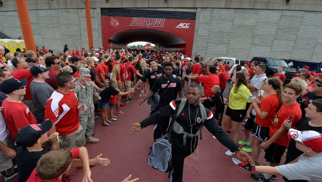 Members of the University of Louisville football team greet the fans during the Card March before their NCAA college football game against Murray State Saturday, Sept. 6, 2014 at Papa John's Cardinal Stadium in Louisville, Ky. (AP Photo/Timothy D. Easley)