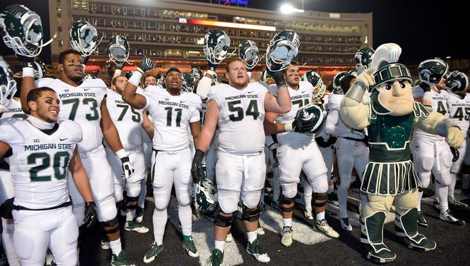 Michigan State's Connor Kruse (54), Dennis Finley (73), Jamal Lyles (11), Nick Hill (20) and others celebrate a 37-15 win over Maryland Saturday night. They were happy to get the win, but not overjoyed by their circumstances.