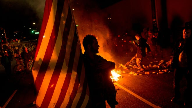 James Cartmill holds an American flag while protesting in Oakland, Calif., on Monday, Nov. 24, 2014, after the announcement that a grand jury decided not to indict Ferguson police officer Darren Wilson in the fatal shooting of Michael Brown, an unarmed 18-year-old. Several thousand protesters marched through Oakland with some shutting down freeways, looting, burning garbage and smashing windows.