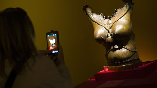"""A woman takes pictures of a sculpture as she visits the exhibition """"The Kama-Sutra: Spirituality and erotism in Indian art,"""" at the Paris' pinacotheque on Oct. 1, 2014 in Paris."""