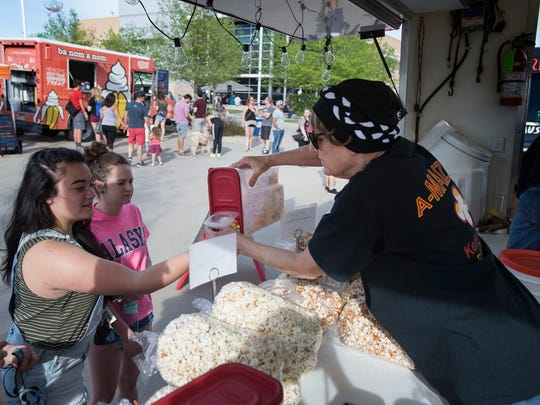 A-MAIZE'N KETTLE CORN food truck owner and operator Jan Frumes hands out samples of her freshly popped corn on Wednesday, May 9, 2018, in Fort Collins, Colo. Frumes, who has been going through chemotherapy for multiple breats cancer tumors, was able to utilize the wig modification services at Mane Door Salon to help her wigs fit and look more natural while she battles cancer.