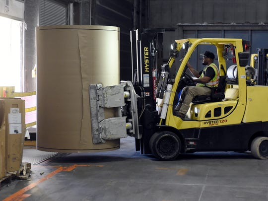 International Paper employee Damien Young uses a clamp truck to transport a roll of paper onto a trailer while working at the plant in Henderson recently.  The plant makes almost 700 tons of paper a day by using recycled boxes and making them into paper.
