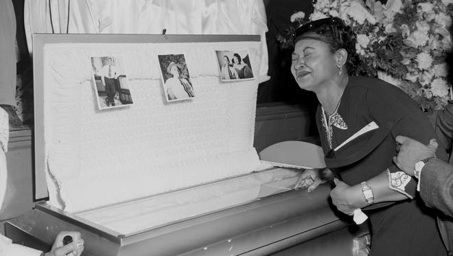 In this 1955 file photo, Mamie Mobley, mother of Emmett Till, pauses at her son's casket at a Chicago funeral home. The 14-year-old Chicagoan was killed in 1955 after reportedly whistling at a white woman during a visit to his uncle's house in Mississippi.