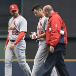 Apr 16, 2014; Milwaukee, WI, USA;   St. Louis Cardinals pitcher Joe Kelly (center) walks off the field with manager Mike Matheny (left) and trainer Greg Hauck (right) after Kelly was injured trying to bunt for a hit in the fifth inning at Miller Park. Mandatory Credit: Benny Sieu-USA TODAY Sports