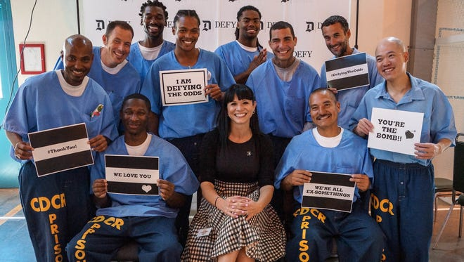Graduates of Defy Ventures' entrepreneurship training at California State Prison in Lancaster are pictured with the nonprofit's founder and CEO, Catherine Hoke.