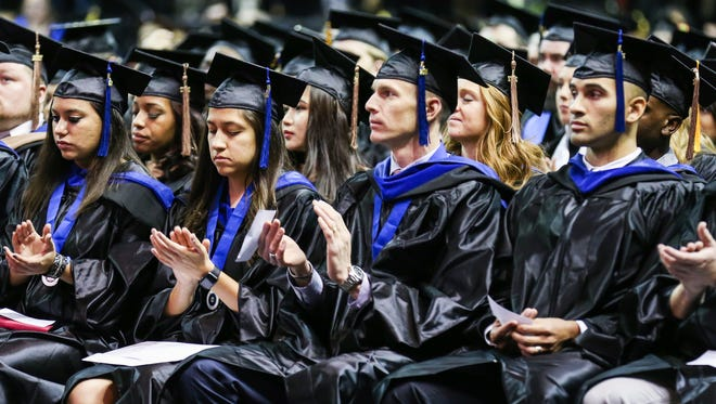Angelo State University graduates applaud the speaker during the commencement ceremony Saturday, Dec. 16, 2017, at Junell Center.