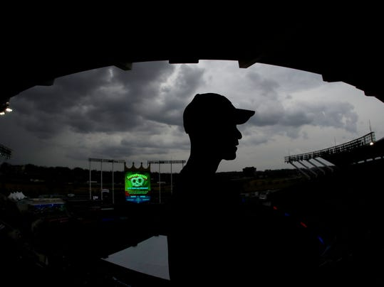Zack Hample, from New York, watches storm clouds from the upper deck at Kauffman Stadium before a baseball game between the Kansas City Royals and the Los Angeles Angels, Friday, April 13, 2018, in Kansas City, Mo. (AP Photo/Charlie Riedel)