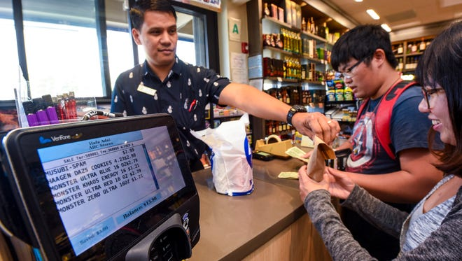 Assistant Manager Alfred Asahan, left, assist customers making a purchase at an ABC Store in Tumon on Tuesday, March 20, 2018.