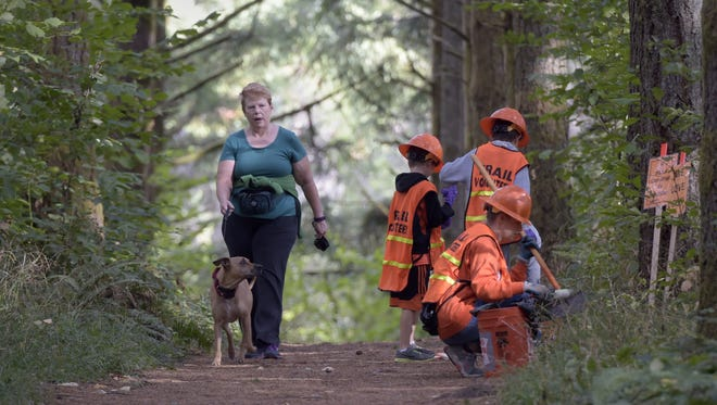 Cyndie Shaner of Corvallis walks her dog, Calie, past volunteers Jana Gordon and her sons Cooper, 8, and Scotty Brennan, 8, as they clean up the trail. Saturday was the day when volunteers collected the piles of orange-painted poop, weeks after they painted them to call attention to the problem.