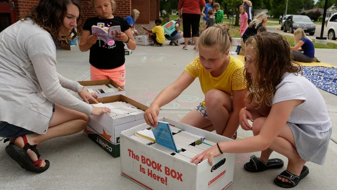 Fourth-grade teacher Mariah Weber helps Lily Schreck, Lila Murphy and Kara Cummings pick out a couple of books Thursday, June 22, 2017, during the Books on Wheels kickoff at Emmeline Cook Elementary School in Oshkosh. Emmeline Cook teachers and staff read stories to neighborhood students at the school and various locations around the neighborhood. Students may keep the books they choose to read in order to encourage summertime reading.