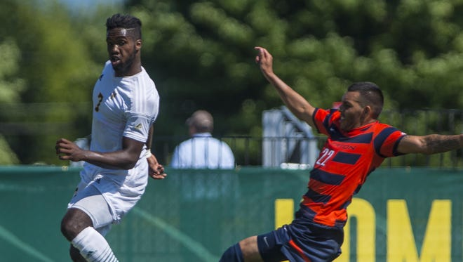 The University of Vermont's Brian Wright, left, passes the ball under pressure from Cal State Fullerton's Ricardo Covarrubias in Burlington on Aug. 26.