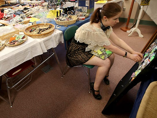 Volunteer Thea Reinert puts together a display board during set-up for the annual Bainbridge Island Rotary Auction in 2016.