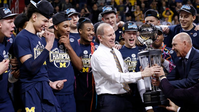 Michigan basketball coach John Beilein accepts the trophy from Big Ten commissioner Jim Delany, right, after defeating Wisconsin for the conference tournament title Sunday, March 12, 2017, in Washington.