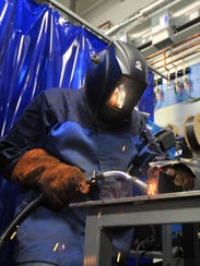 Student Debi White, 26, of Wausau, welds to join two