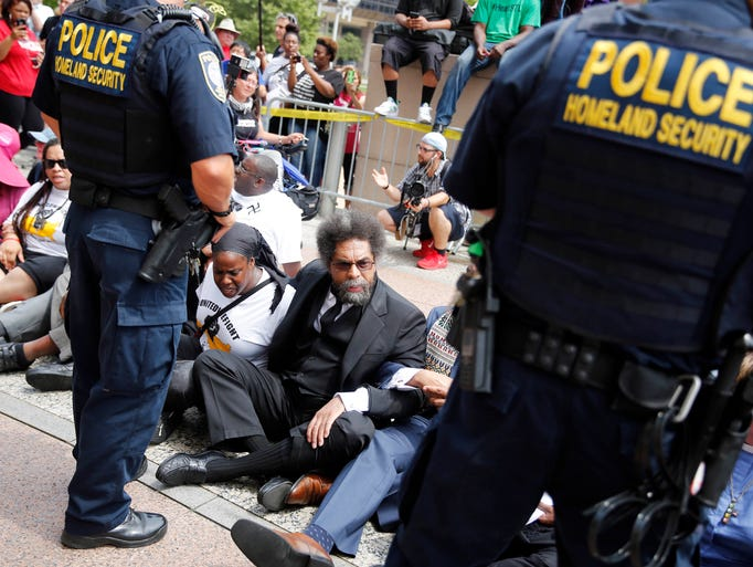 Cornel West, center, joins other protesters as they
