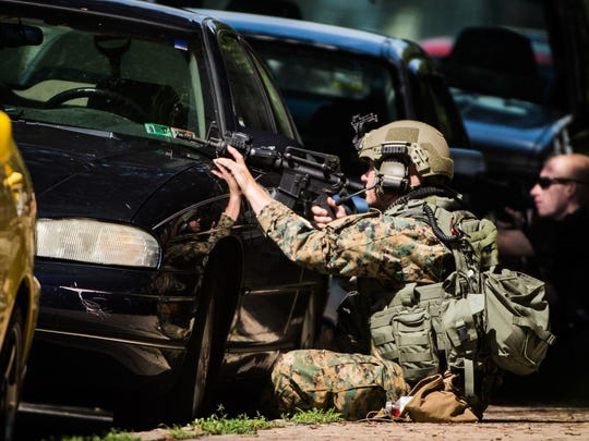 A member of the Lebanon County Emergency Services Unit points his rifle toward 910 Walnut St., where a domestic dispute led to a police standoff.