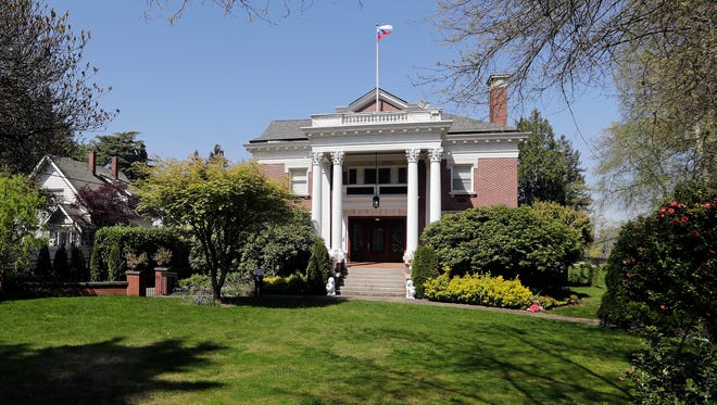 """A Russian flag continues to fly from the roof of the former Russian consul general's residence in Seattle last month. There's a diplomatic fight over the now-closed Russian consulate's flag in Seattle. U.S. State Department officials said it """"respectfully"""" lowered the Russia flag Saturday, April 28, 2018, from the Russian consul-general residence property after the mansion was vacated last month. The Russian Embassy has demanded it be put back, accusing the U.S. of """"unacceptable treatment"""" of their national symbol."""