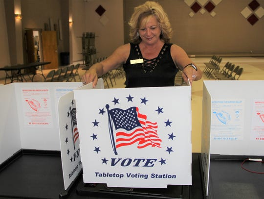 Otero County Clerk Robyn Holmes sets up one of the