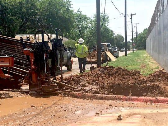 Crews work to repair a water main break outside of