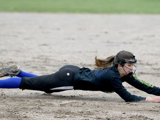 Olympic High School softball senior player Lauren Valez makes a diving catch in practice.