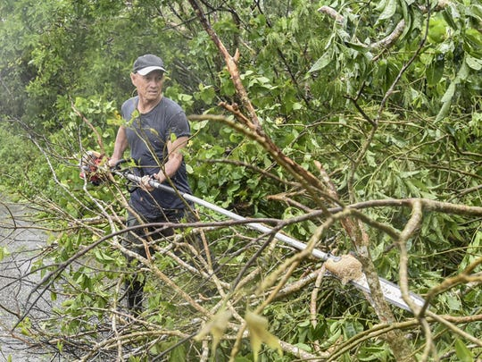 Dededo Vice Mayor Andrew Benavente uses a buscutter with a chainsaw attachment to clear the southbound lane of Route 3 in Dededo on May 16 following Typhoon Dolphin.