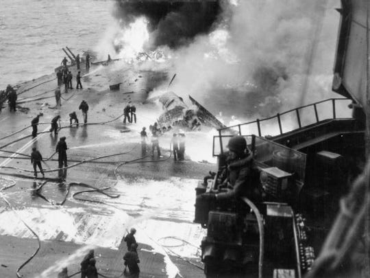Crew members work to put out fires and fix damage caused by kamikaze crash.