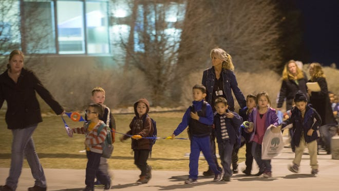 Kids from Manzano Vista Elementary school are led by teachers to an area where their parents were waiting during the hunt for an active shooter in south west Albuquerque, New Mexico, Monday Dec. 1, 2014.  (AP Photo/Albuquerque Journal, Roberto Rosales)