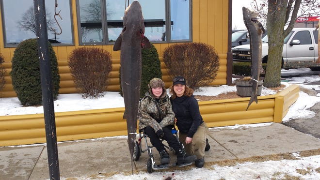 Kevin Kollmann, 14, and his mom Karen Kollmann, stop at Wendt's on the Lake to check out the sturgeon displayed outside the business during opening weekend of spearing. Kevin, who lives with a form of cerebral palsy, helped his mom when she speared a sturgeon the following weekend. Kevin was invited to go spearing as part of the Fishing Has No Boundaries inaugural event this year.