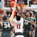 MSU's Branden Dawson, right, blocks a shot from Louisville's Mangok Mathiang during Sunday's NCAA Elite Eight game in Syracuse, N.Y. Dawson finished with four blocks. At left is MSU's Gavin Schilling.