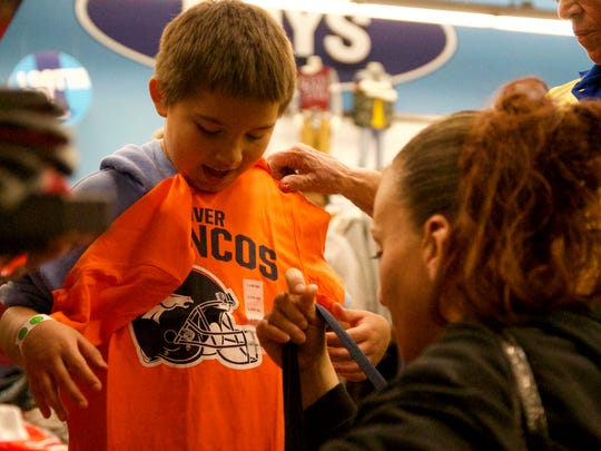 Juan Chavez and his mother, Holly Dominguez, pick out Denver Broncos T-shirts during Dress the Child event in 2017.