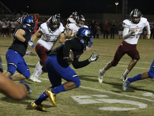A Chandler defender runs after picking up a fumble
