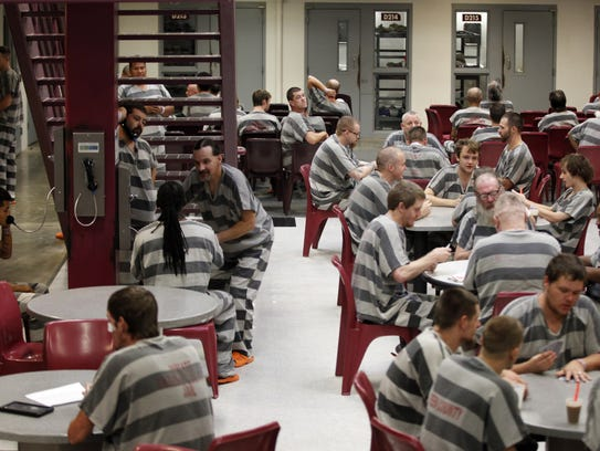 Inmates sit inside the D Pod of the Greene County Jail