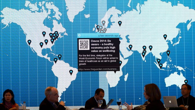 Participants sit in front of a world map on the eve of the opening of the Annual Meeting of the World Economic Forum, WEF, in Davos, Switzerland on Tuesday.