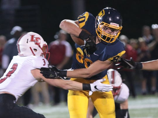 Moeller's Brendan Bates (80)  runs the ball during the Crusaders' 24-28 loss to La Salle  Friday, Sept. 29, 2017.