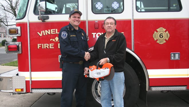 Mark A. Cifaloglio, (left) captain, Vineland City Fire Department, accepts a donation of a battery operated Stihl rotary saw from Gary Galloway, president of Rental Country.