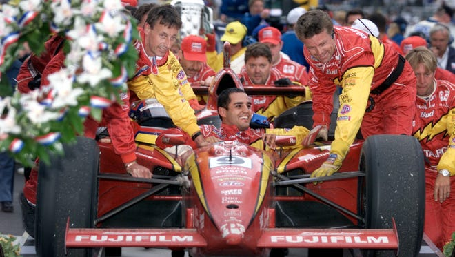Juan Montoya's crew celebrates as they push his car up the ramp to victory lane after he won the Indianapolis 500-MIle Race.