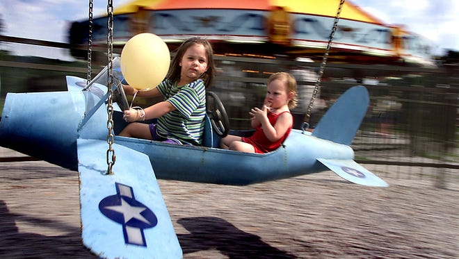 Madeline Robinson, left, and her cousin Kelsey Robinson take flight at City Park Amusment Rides in Iowa City. Families like the Robinsons filled local parks taking full advantage of he pleasant weather of Labor Day, Sept. 3, 2001.