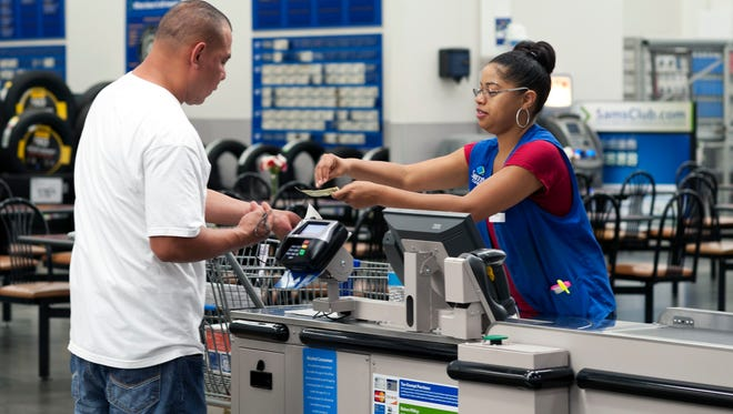 Conquisia Tyler, right, gives change to a customer at Sam's Club in Bentonville, Ark.