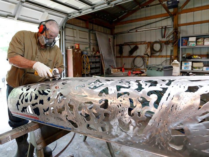 Artist Bob Parker polishes an old aluminum canoe that