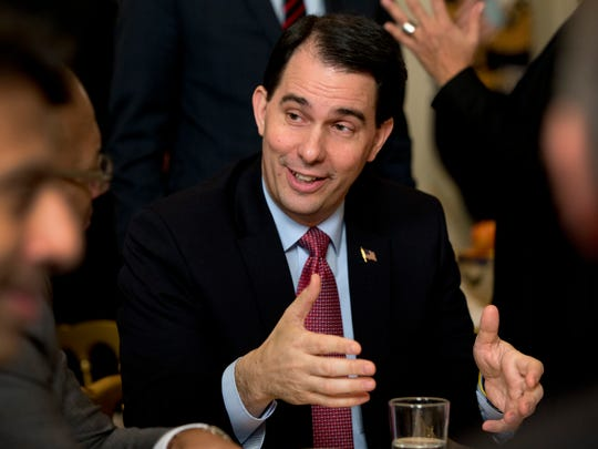 Wisconsin Gov. Scott Walker talks at his table at the